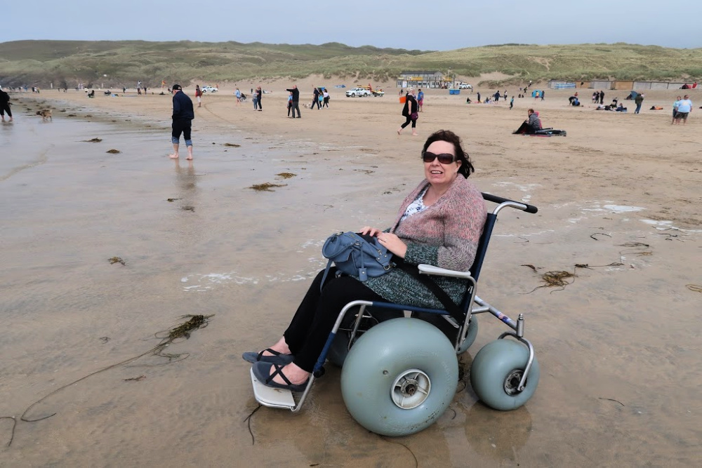 Me in a wheelchair on the beach at Perranporth, Cornwall. The beach has people in the background. The beach wheelchair has big bouncy wheels ,