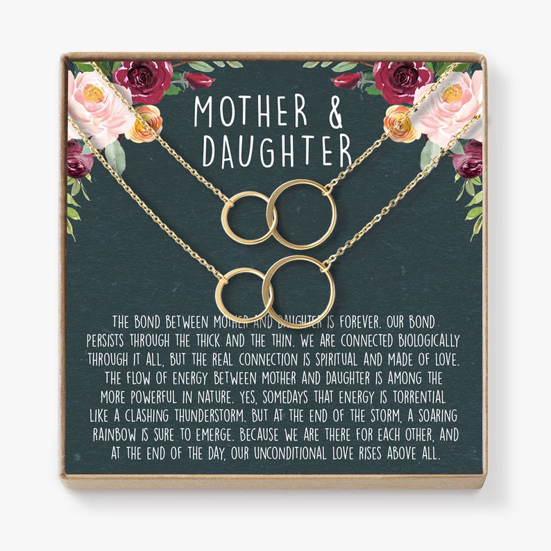 twin necklaces for mother and daughter on flower background card.