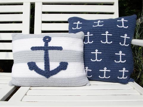 image shows both the square striped cushion with a large anchor and the blue cushion with small white anchors.
