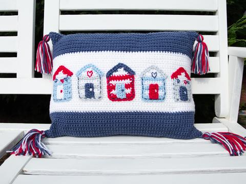 image shows a blue and white cushion with a row of blue, white and red beach huts in a nautical theme.