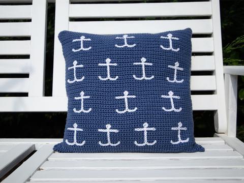 image shows a dark blue cushion with mini white anchors