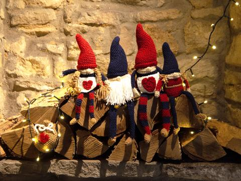 Four Christmas crochet gnomes in blue and red sitting on logs against a brick wall