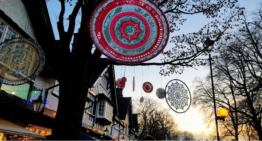 a selection of crochet mandalas hanging from trees in the twilight.