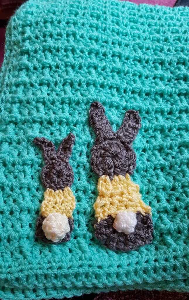 baby blanket crochet in waffle stitch, with two little bunnies sewn on