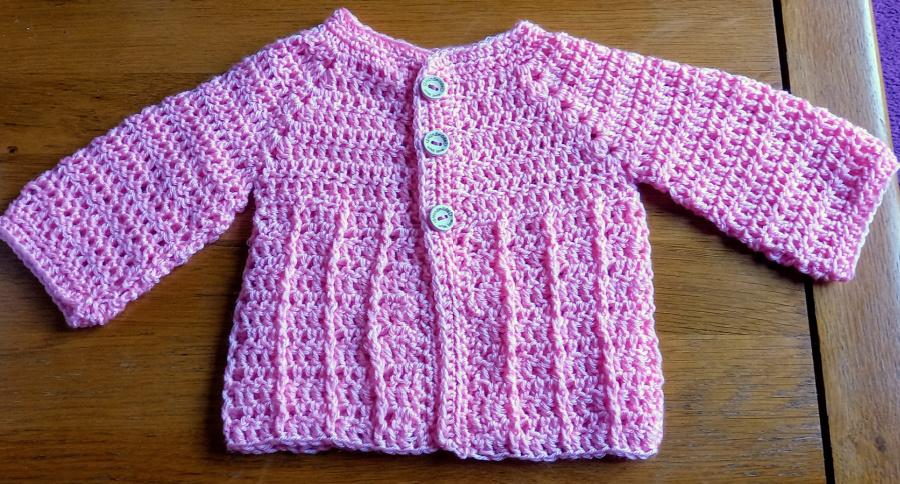baby cardigan in pink from the front with arms out