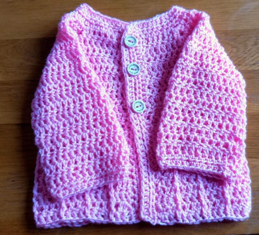 baby cardigan in pink with arms folded in
